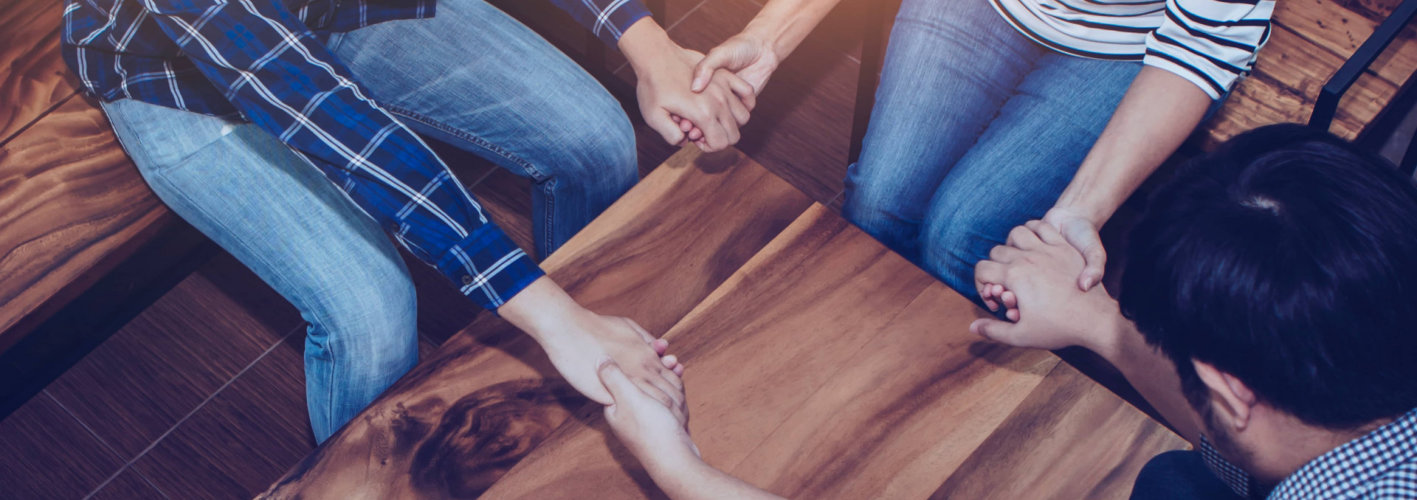 three people holding hand each other and pray together around wooden table, christian prayer group or team work concept
